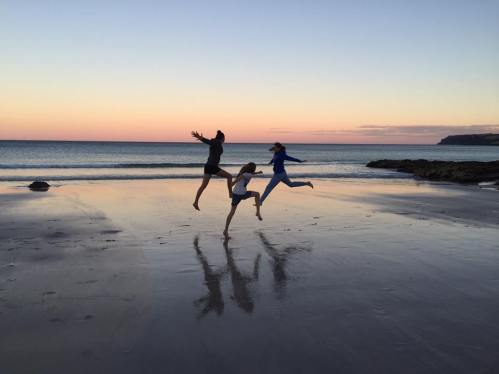 Girls leaping on sunset beach, BH